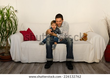 Baby and father watching tv and smiling on a white sofa with red pillow and little bear