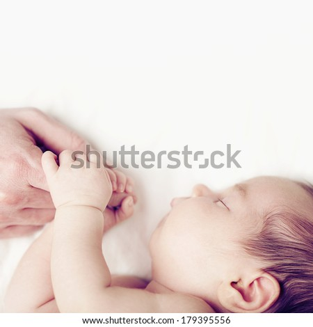 Baby and fathers hand, parental love - stock photo