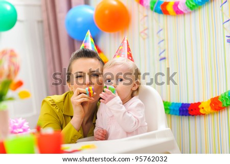 Baby and mother blowing into party horn - stock photo