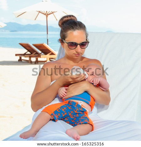Baby and mother feeding on sunbed - stock photo
