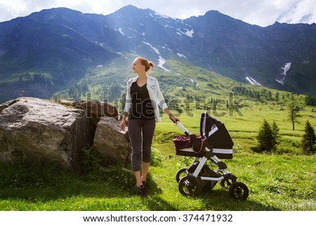 Baby and mother with the Alps mountains in nature in the background - stock photo