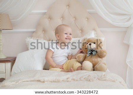 baby and teddy bear on the bed in the bedroom upon awakening