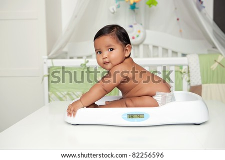 Baby and weight in nursery room - stock photo