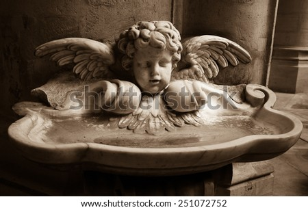 Baby angel over holy water stoup in church. Aged photo. Sepia.