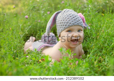 Baby as a bunny or sheep on green grass outdoors. - stock photo