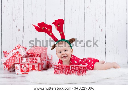 Baby as raindeer laying and smiling next to gifts - stock photo