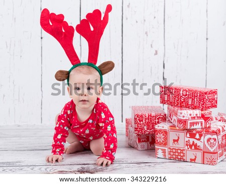 Baby as raindeer sitting next to gifts