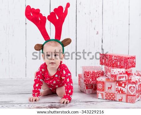 Baby as raindeer sitting next to gifts - stock photo