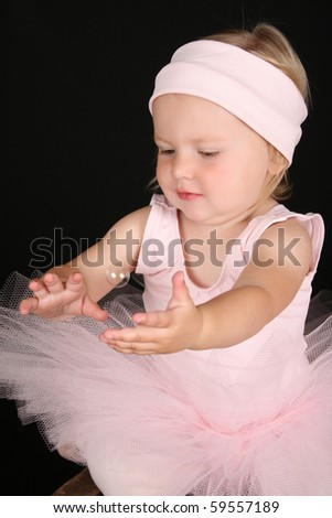 Baby ballerina catching a single floating bubble - stock photo