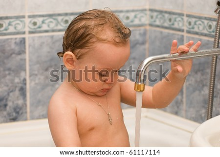 Baby bathes in the bath - stock photo
