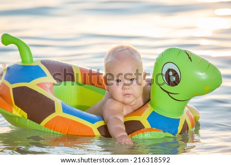 Baby bathing in the sea with swim ring - stock photo