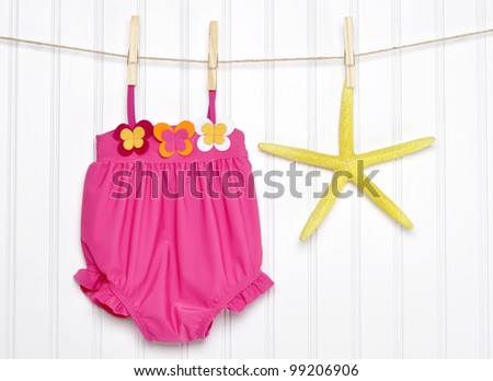 Baby Bathing Suit and Starfish on a Clothesline Summertime Concept - stock photo