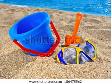 Baby beach toys on the sand against the blue sea - stock photo