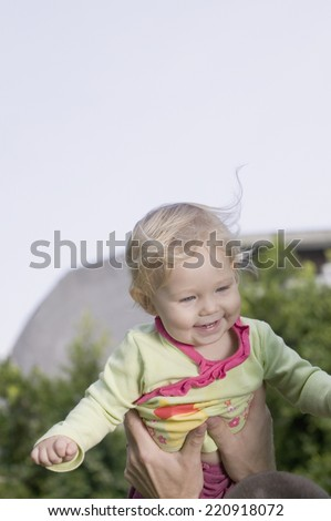 Baby being held up outdoors - stock photo