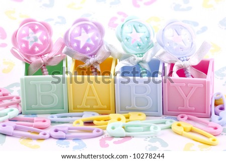 Baby blocks with rattles and safety pins on a footprint background - stock photo