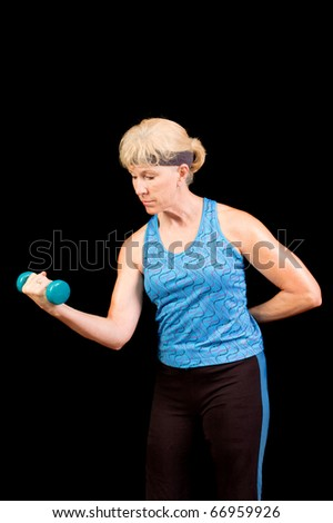 Baby boomer woman exercising using weights over a black background - stock photo