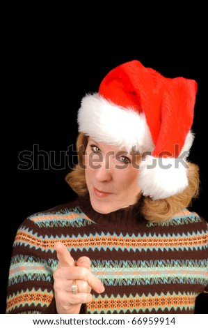 Baby boomer woman with a scolding look and pointing has a Santa hat on over a black background - stock photo