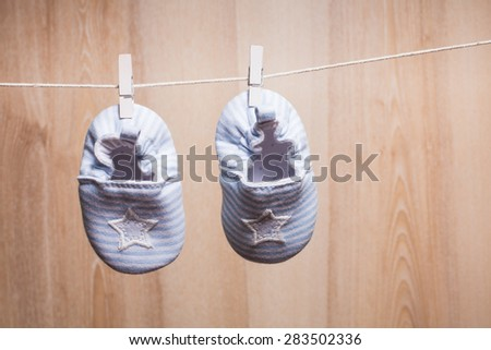 Baby booties attached to the rope - babyshower postcard - stock photo