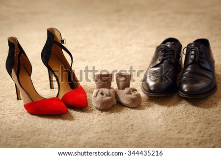Baby booties between parent's shoes. Christmas Atmosphere - stock photo