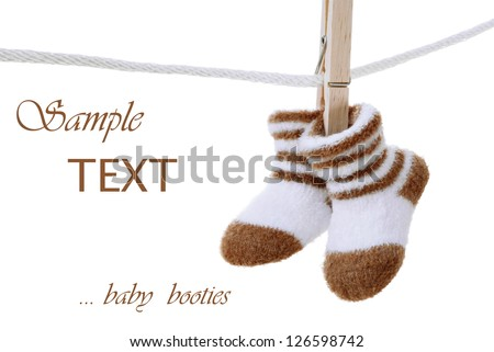 Baby booties hanging on clothesline on white background with copy space. - stock photo