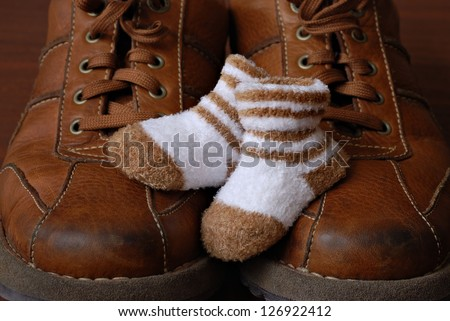 Baby booties nestled on top of parent's well worn leather shoes.  Macro with shallow dof. - stock photo
