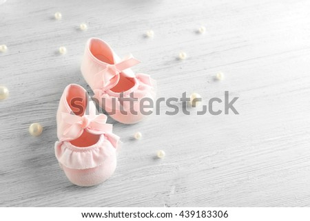 Baby booties on wooden table, closeup - stock photo