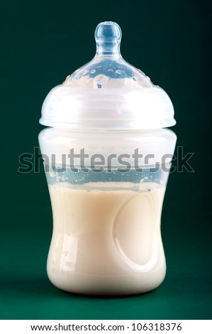 Baby bottle on green background - stock photo