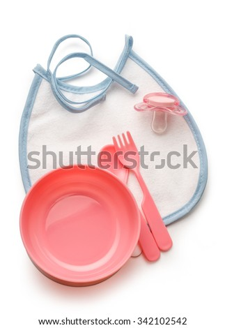 Baby bowl, spoon and fork with dummy and bibs - stock photo