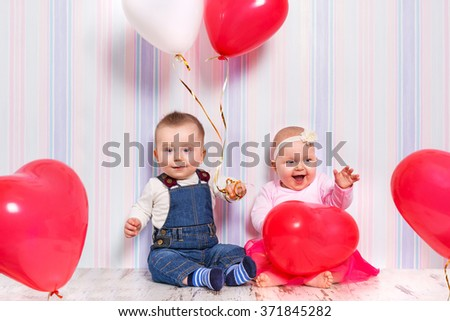 Baby boy and girl playing with hearts. Valentines day. - stock photo