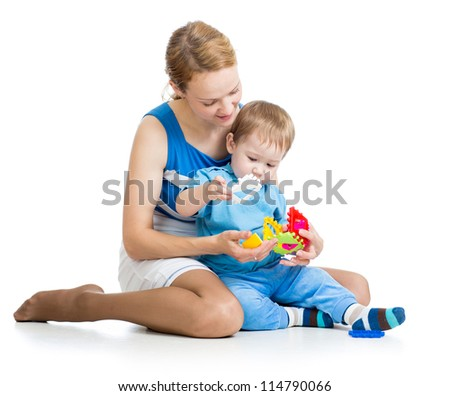 baby boy and mother playing together with puzzle toy - stock photo