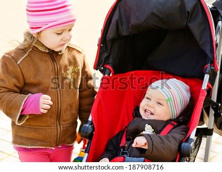 baby boy and toddler girl on the walk - stock photo