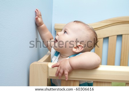 Baby boy at home, standing and playing in his crib - stock photo