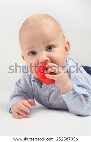 Baby boy biting a red toy - stock photo