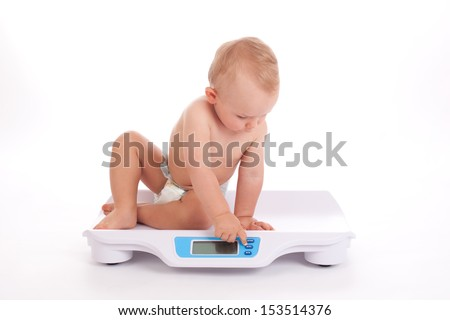 Baby boy check own weight on scales.  White background - stock photo