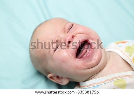 Baby boy crying on the bed at home - stock photo