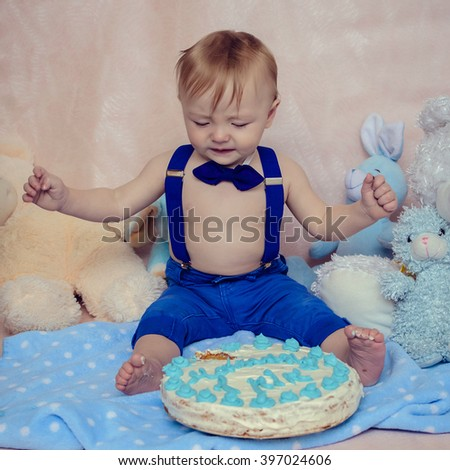 Baby boy crying while eating his birthday party cake. Smash the cake party. Portrait of cute toddler crying while playing smash cake. - stock photo