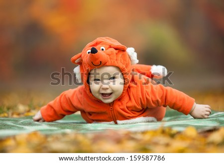 Baby boy dressed in fox costume in autumn park  - stock photo