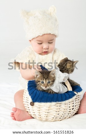 Baby boy dressed in white fur with two small kittens in a basket