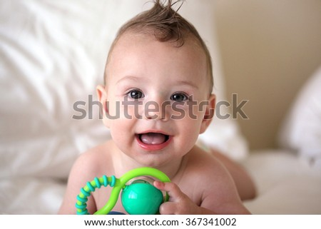 Baby boy drooling while playing with a rattle. - stock photo