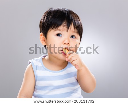 Baby boy eat biscuit and look away - stock photo