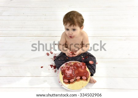 Baby boy eating a birthday cake with his hands - stock photo