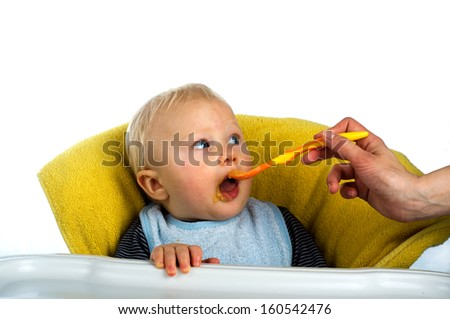 Baby boy eating from spoon - stock photo