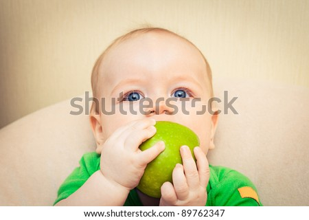Baby boy eating green apple