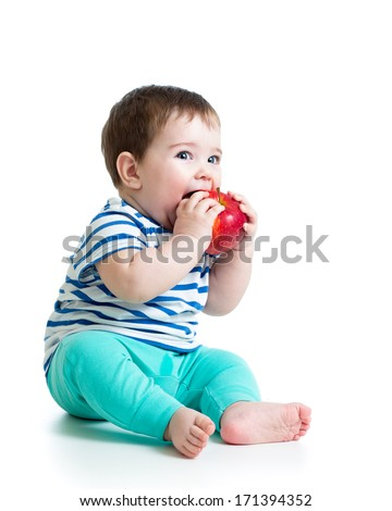 Baby boy eating red apple, isolated on white - stock photo