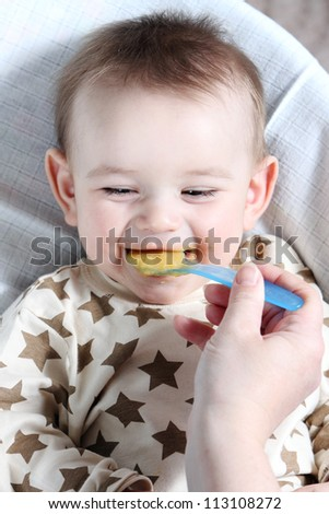 Baby boy eating vegetable mash - stock photo