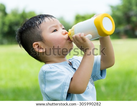 Baby boy feeling so hot and drink with water - stock photo