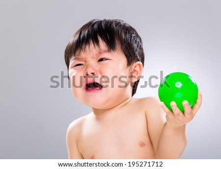 Baby boy feeling unhappy with holding his toy - stock photo