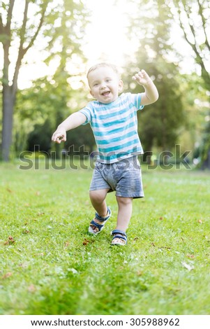 Baby boy first steps - stock photo