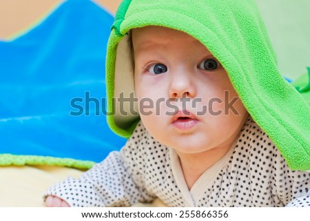 Baby boy hidden under his blanket looking surprised. - stock photo