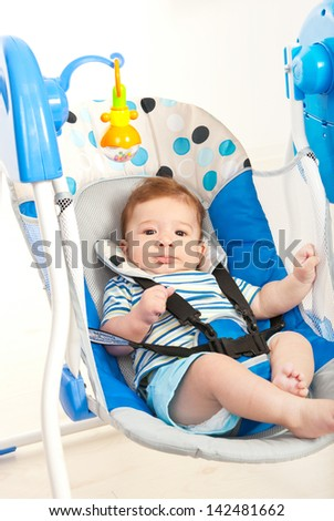Baby boy in a musical swing home against white background - stock photo